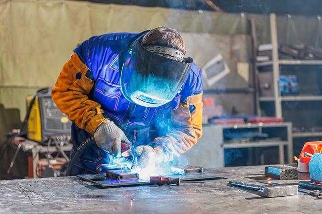 Man welding a metal plate for a custom fabrication job.
