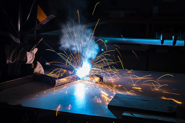 Structural steel fabricator welding in a shop.
