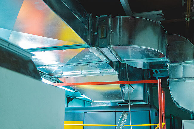Large industrial ductwork in a factory setting.