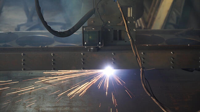 Metal fabrication with sparks flying.