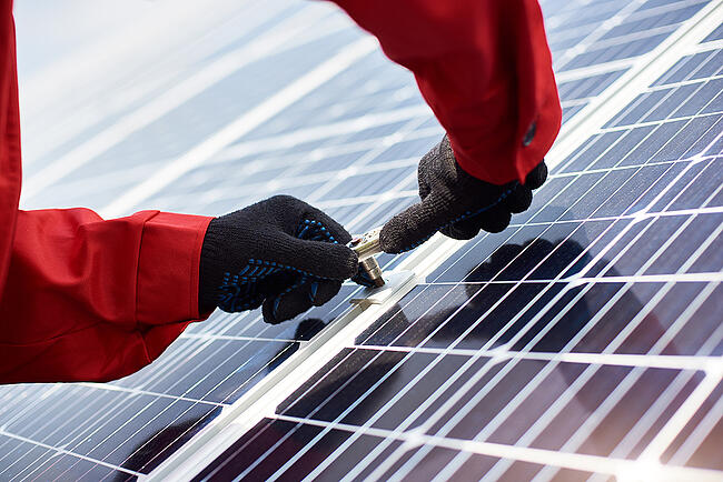 Close-up of hands installing a large solar panel.