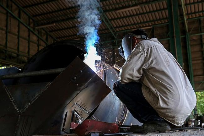 Man welding in a fabrication shop.