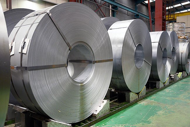 Large rolls of steel being stored in a warehouse.