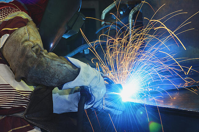 Welder working on steel project.