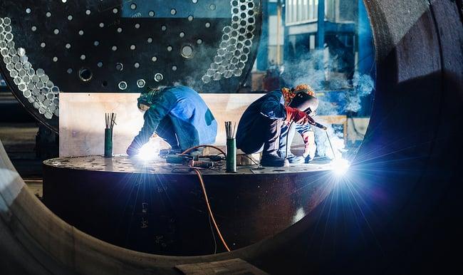 Two welders working on a custom metal fabrication project.