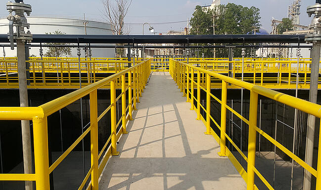 Miles of bright yellow coated industrial exterior steel safety handrail