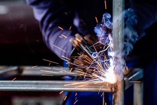 A professional welder working in Swanton Welding, a steel fabrication shop in Toledo, Ohio