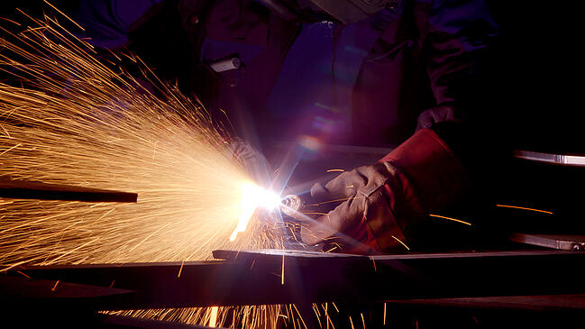 Close up of heavy metal fabricator welding on a project.
